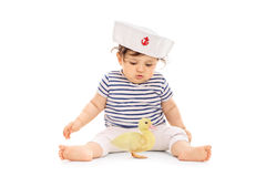 Baby girl in a sailor outfit with a small duckling Stock Photo
