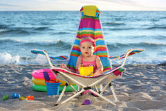 Baby girl on the sand beach with toys Stock Image