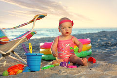 Baby girl on the sand beach with toys Royalty Free Stock Photos
