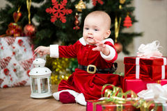 Baby girl Santa Claus in front of Christmas tree Stock Images