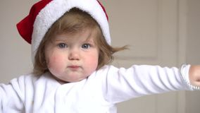Baby girl in Santa Claus red hat at home stock video