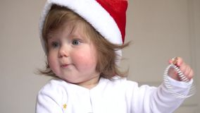 Baby girl in Santa Claus red hat playing stock footage