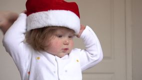 Baby girl in Santa Claus red hat wearing hat stock video