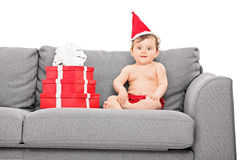 Baby girl with santa hat seated on couch Royalty Free Stock Photo