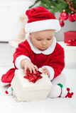 Baby girl in santa outfit opening a present Stock Photo