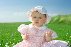 Baby girl sat in flowery field Royalty Free Stock Photos