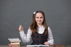 Baby girl in school uniform with peencil. Baby girl in a school uniform sitting at a table with books Royalty Free Stock Photo