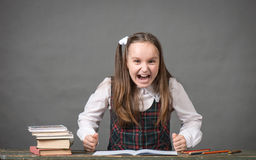 Baby girl in school uniform with peencil. Baby girl in a school uniform sitting at a table with books Royalty Free Stock Photography