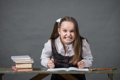 Baby girl in a school uniform sitting at a table with books. And doing homework Royalty Free Stock Images