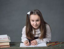 Baby girl in a school uniform sitting at a table with books. And doing homework Royalty Free Stock Image