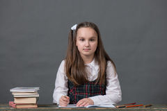 Baby girl in a school uniform sitting at a table with books. And doing homework Stock Images