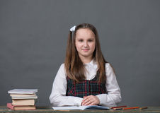 Baby girl in a school uniform sitting at a table with books. And doing homework Royalty Free Stock Photos
