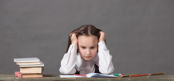 Baby girl in a school uniform sitting at a table with books. Tired baby girl in a school uniform sitting at a table with books and holding his head Royalty Free Stock Photo