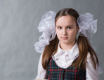 Baby girl in school uniform with white bows Stock Images