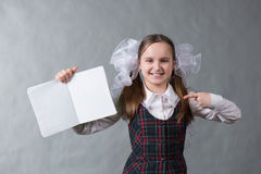 Baby girl in school uniform with white bows. Pointing at an open net notebook Royalty Free Stock Photography