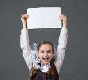 Baby girl in school uniform with white bows. Pointing at an open net notebook Royalty Free Stock Images