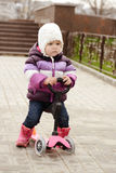 Baby girl on scooter Stock Photos