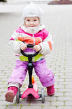 Baby girl on scooter. In the park stock photography