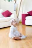 Baby girl seated on a floor. Happy eight month old baby girl seated on a hardwood floor in living room Royalty Free Stock Photography