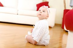 Baby girl seated on a hardwood floor Royalty Free Stock Images