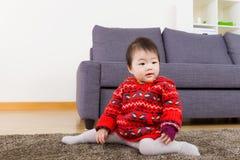 Baby girl seating on carpet Royalty Free Stock Image