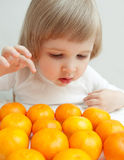 The baby girl is selecting a tangerine Stock Photo