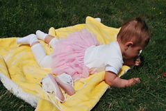 Baby girl. Seven-month baby girl lies on a yellow blanket among green grass stock images