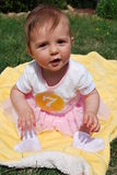 Baby girl. Seven-month baby girl sitting on a yellow blanket among green grass royalty free stock images