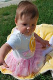 Baby girl. Seven-month baby girl sitting on a yellow blanket among green grass stock photo