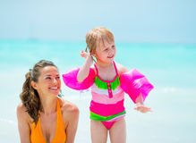 Baby girl shaking out water from ear on beach Royalty Free Stock Images