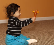 Baby Girl Shaking a Wooden Rattle Royalty Free Stock Photos