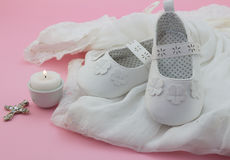 Baby girl shoes, cross and candle on white lace with pink backgr Stock Photo