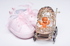 Baby girl shoes and miniature baby buggy Royalty Free Stock Photo