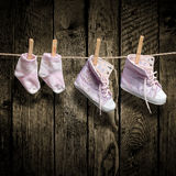 Baby girl shoes and socks on the clothesline Royalty Free Stock Image