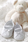 Baby girl shoes and teddy bear Royalty Free Stock Image
