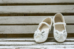 Baby girl shoes on wooden background, vintage color tone. Royalty Free Stock Photography