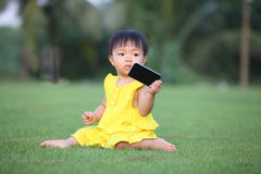 A baby girl show her smartphone and sit on lawn Stock Photography