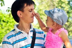Baby girl showing father's nose Stock Image