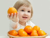 The baby girl is showing the tangerine Stock Photography