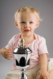 Baby girl with silver trophy. On a gray background stock photo