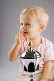 Baby girl with silver trophy. On a gray background royalty free stock images