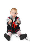 Baby girl singing. Sweet one year old baby girl with blue eyes singing with a microphone in her hand isolated on a white background Royalty Free Stock Photo