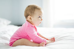 Baby girl sit on white sheet Stock Photos