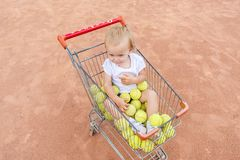 Baby girl sits in a basket with tennis balls on clay court. stock photos