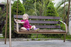 Baby girl sits on  swing in park Stock Photos