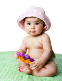 Baby girl sitting. Beautiful cute Caucasian Hispanic baby girl sitting on green blanket holding an orange with purple teething ring toy, wearing pink hat Royalty Free Stock Photo