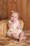 Baby Girl Sitting Against a Straw Bale Stock Image