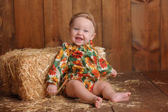 Baby Girl Sitting Against a Straw Bale Stock Images