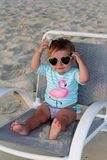 Baby girl sitting on a beach chair Royalty Free Stock Photos