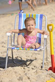 Baby girl sitting on a beach chair Stock Photos